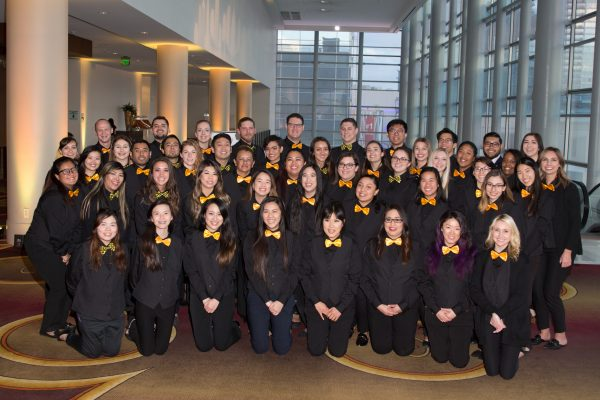 Group photo of student volunteers dressed in black slacks, black button-up shirts, black vests, and yellow bowties lined up in rows.