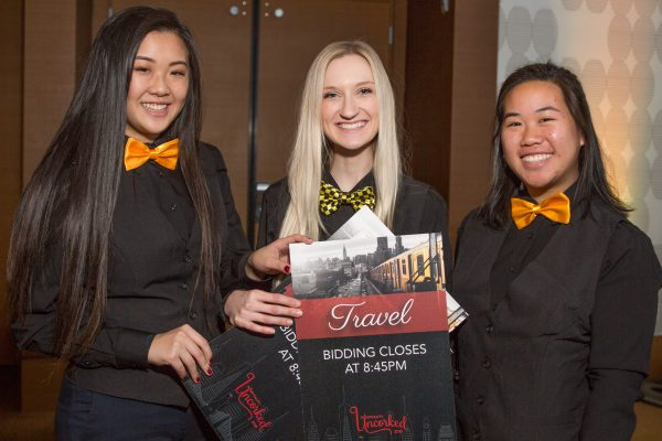 Three student volunteers holding silent auction signage, pose for a photo while setting up the event reception.