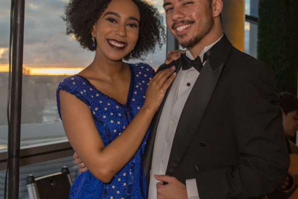 Two Theater Department students dressed in black-tie style costumes during the event reception pose for a photo together.