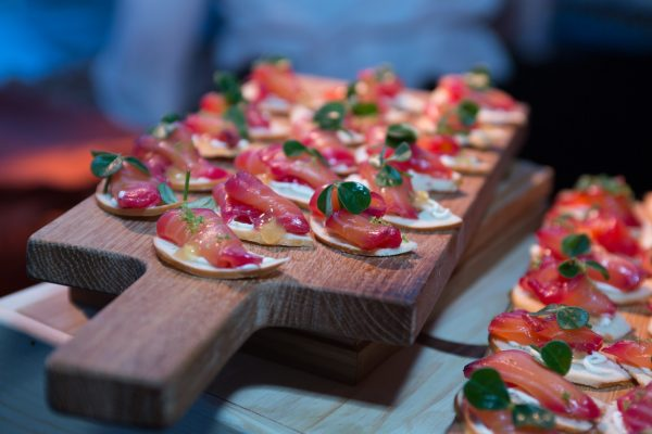 A wooden board lined with many small Applewood Smoked Rose Cured Salmon hors d'oeuvres made of vibrant red salmon placed on a crispy chip, topped with apple gelee, citrus creme, and a green leaf garnish.